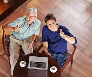 Mann und Senior im Café halten Daumen hoch