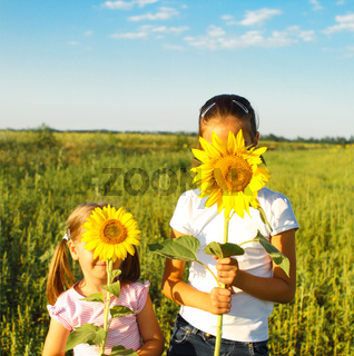 Two cute litle girls hiding behind sunflowers