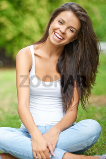 Happy young brunette relaxing in park