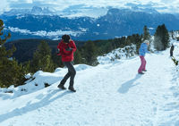 Family plays at snowballs on winter mountain slope