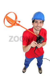 Tradesman holding up a tool for mixing mortar