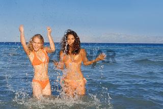 people splashing in sea on summer holiday