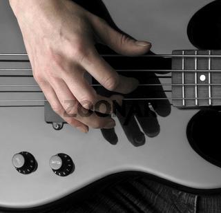 hand on bass guitar
