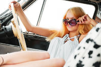 Young blond woman relaxing in a retro car
