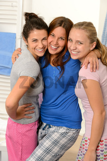 Three teenage girls laughing in pajamas