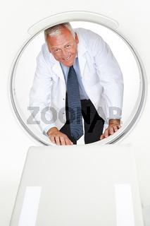 Arzt schaut durch Röhre eines MRT