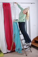 Young woman hanging up curtains - danger