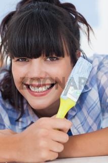 Pretty woman lying on floor holding paint brush