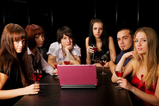 Young people with laptop in a night bar
