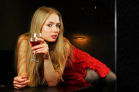 Beautiful blond woman lying on the bar counter