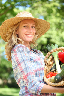 Woman smiling with a straw hat holding basket of vegetables.