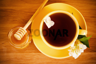 The top view on a cup of tea with a flower of a jasmin and honey
