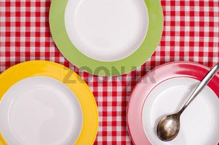Drei bunte Teller und ein Löffel