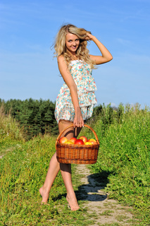Rural landscape with beautiful blonde walking at the meadow.