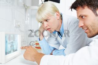 Radiologe und Zahnarzt schauen auf Panoramaschichtaufnahme