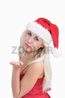 Woman wearing santa hat as she blows kiss