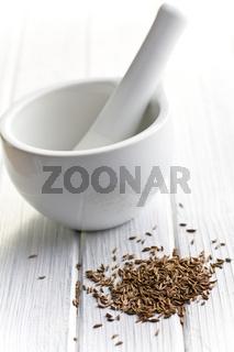cumin seeds and ceramic mortar