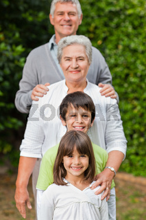 Grandparents with their children looking at the camera in the garden