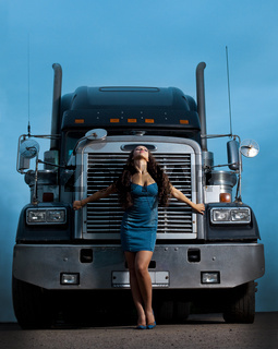Young pretty girl posing before huge cargo truck