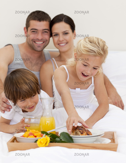 Family eating breakfast in bedroom