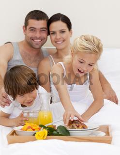 Family eating breakfast in bedroom
