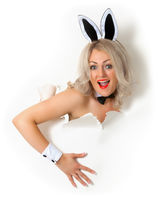 Cheerful girl in bunny suit looking out of hole