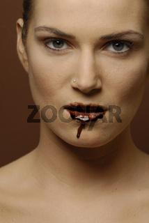 junge Frau mit Schokolade auf den Lippen