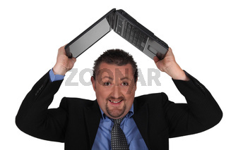Man lifting computer over his head
