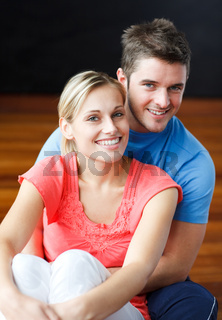 Lovers sitting together on the floor and smiling