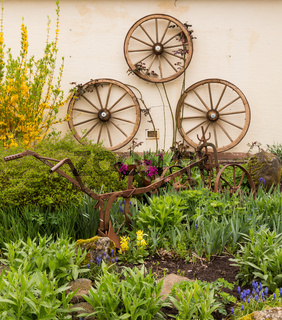 Rural garden decorated with cart wheels
