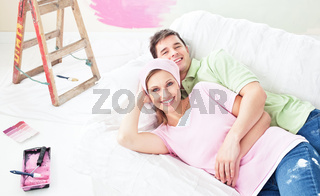 Positive couple lying on a sofa after painting a room