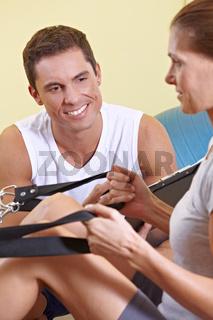 Fitnesstrainer betreut Frau