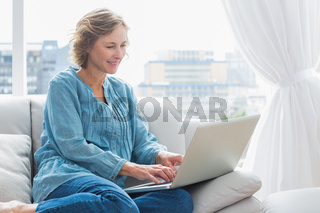 Happy blonde woman sitting on her couch using laptop