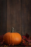 Large pumpkin with leaves against a wood backgroun