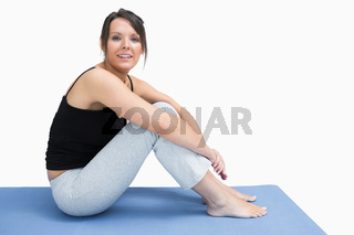 Side view of young woman in sportswear sitting on yoga mat
