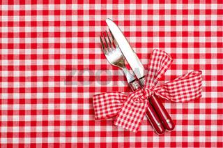 Messer und Gabel mit rot karierter Schleife