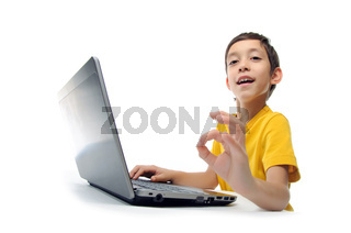 young boy in yellow t-shirt with laptop showing ok at camera isolated on white background