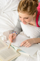 Teenage girl concentrating on studying in bed