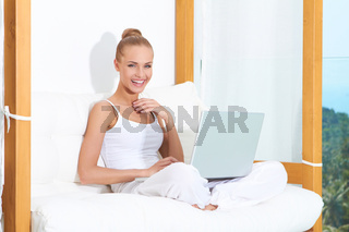 Joyful woman laughing with laptop