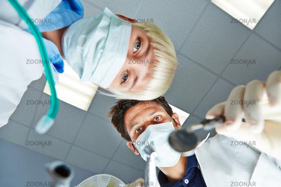 Zahnarzt und Zahnarzthelferin bei Behandlung
