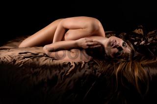 Nackte blonde junge Frau im Bett mit brauner Seid