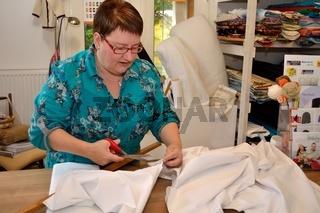 Textilwarenverkaeuferin schneidet Stoff