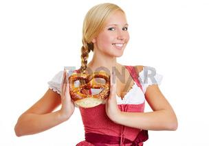 Glückliche Frau im Dirndl mit Brezel