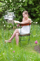 Young woman in white summer dress sitting in a garden and reading a book