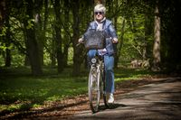 Senior runs with her bike on a forest trail