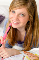 Smiling teenage girl daydreaming over her diary