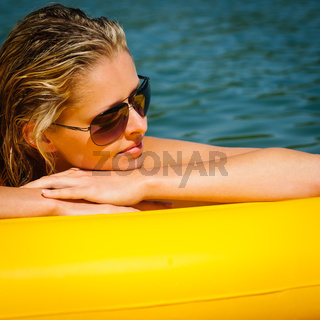 Summer woman lying on yellow floating mattress