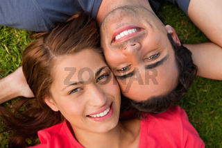 Close-up of two friends looking upwards while lying head to shoulder