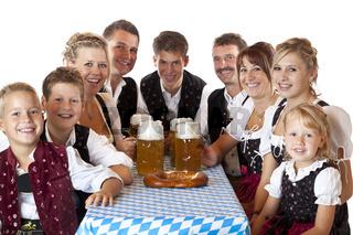 Bayrische Familien in Tracht stossen mit Oktoberfest Bier an.