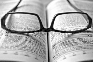 schwarze Brille auf einem Lexikon
